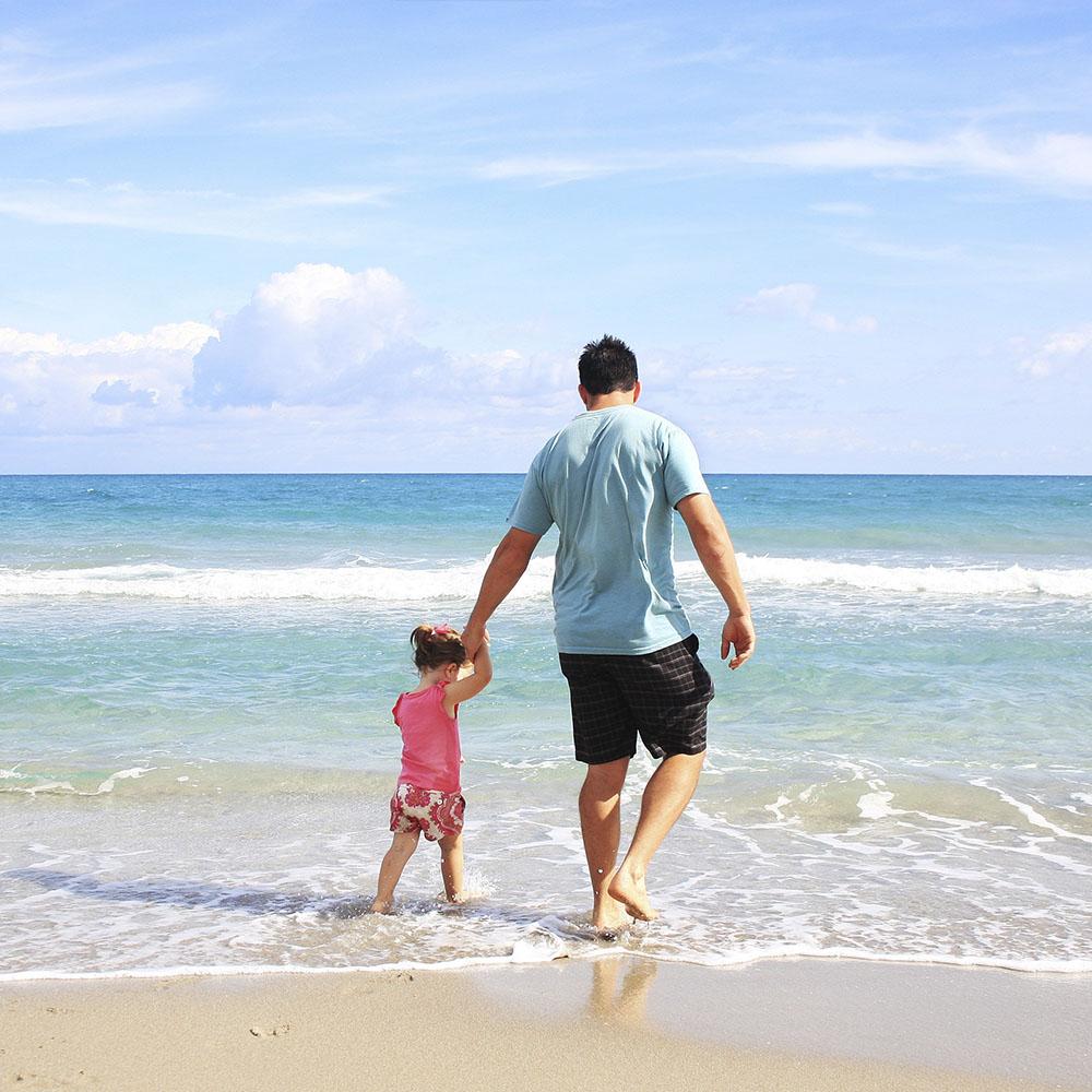 Padre e hija paseando por la playa